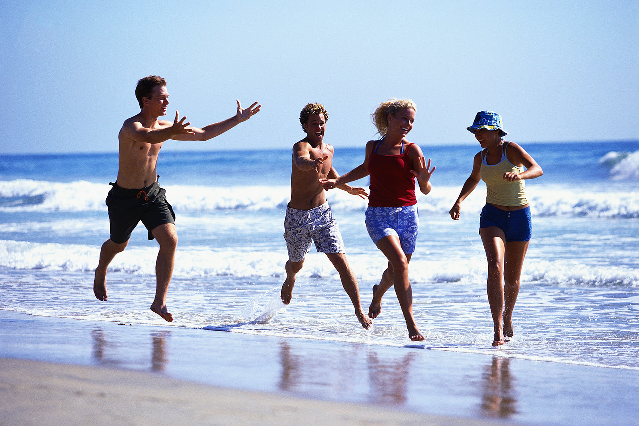 Young Men Chasing Young Women at Beach